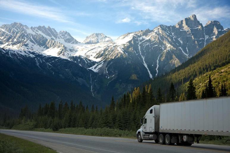 Ein LKW fährt auf einer Landstraße, im Hintergrund sieht man Gebirge